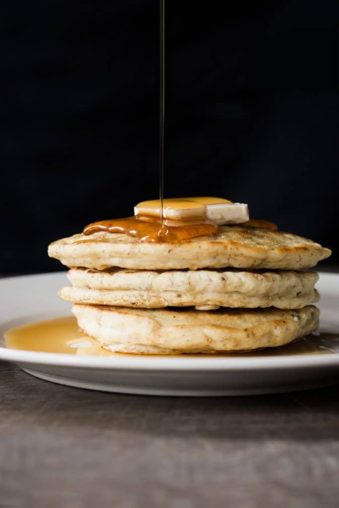 A stack of vegan pancakes with syrup being poured on them.
