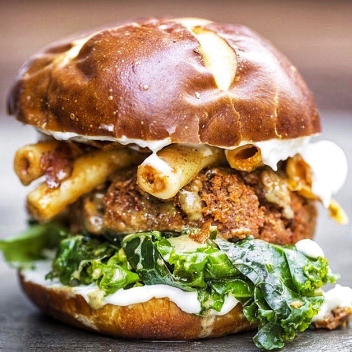 Smoked sage seitan burger with coconut bacon, smoked sage seitan sausage baked ziti, marinated kale and roasted garlic aioli on a grilled pretzel bun from Cinnamon Snail