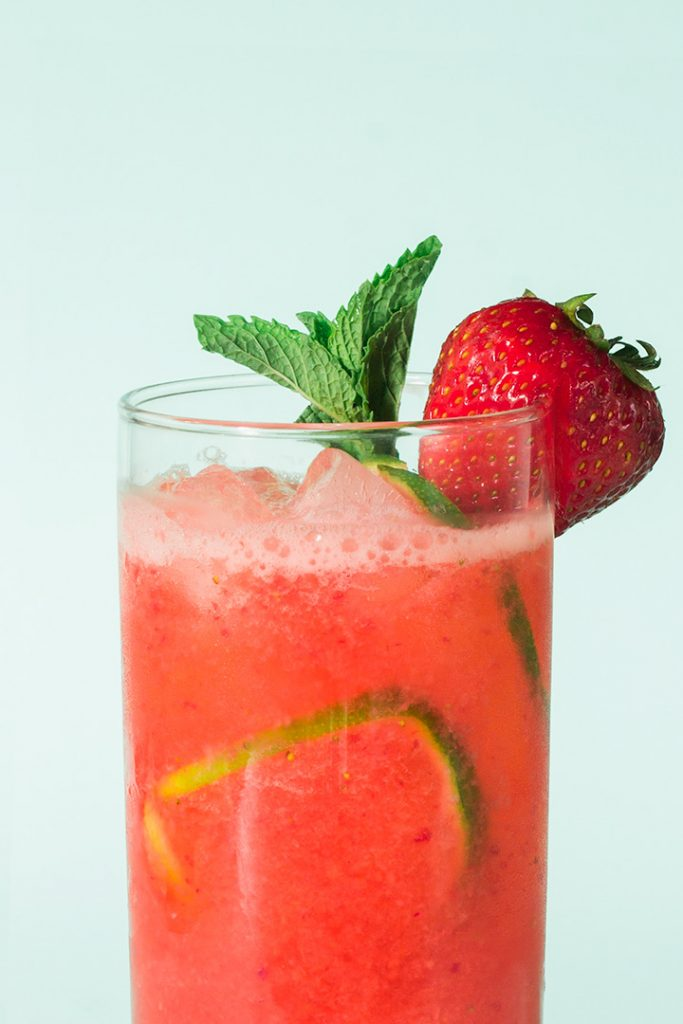 Close up of a glass of limeade with a sprig of mint and a strawberry on the glass.