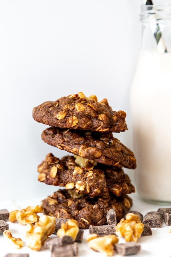 A stack of double chocolate cookies next to walnuts and chocolate chunks. Recipe from Veganosity