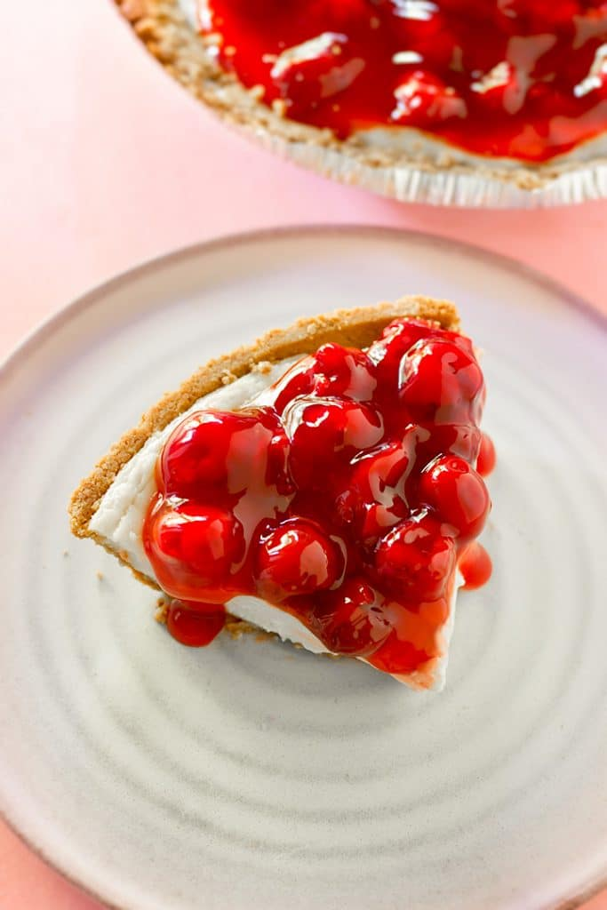 A slice of baked vegan cheesecake covered in cherries.