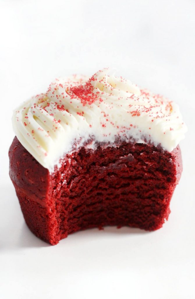 A gluten-free red velvet cupcake with a bite taken out of it.