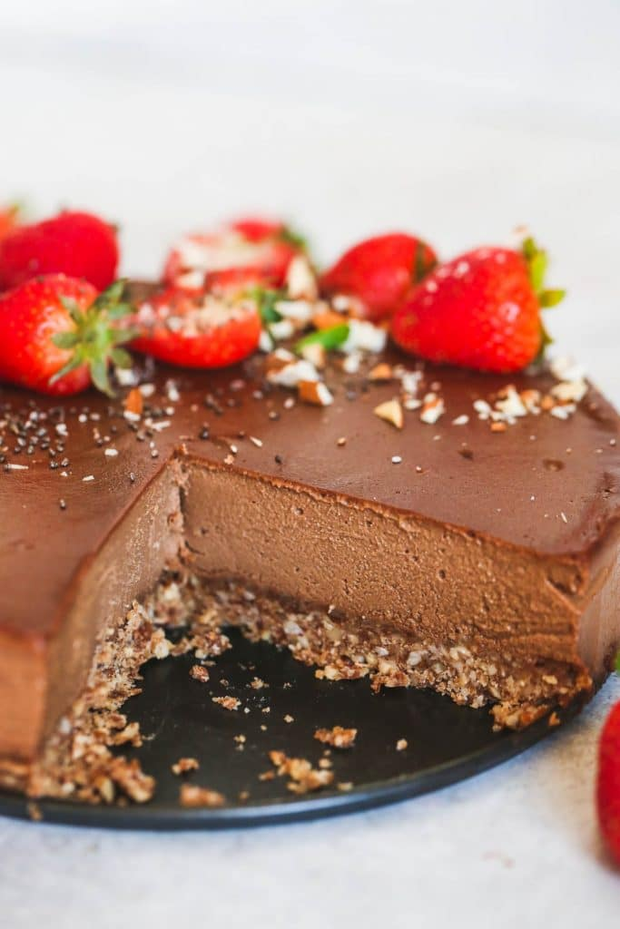 A chocolate cheesecake with a slice missing.