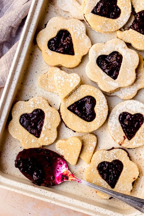 A baking sheet full of jam filled linzer cookies.