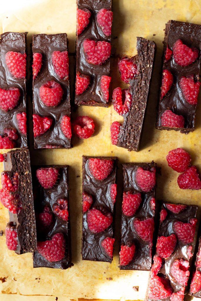 Slices of brownie bars covered in raspberries.
