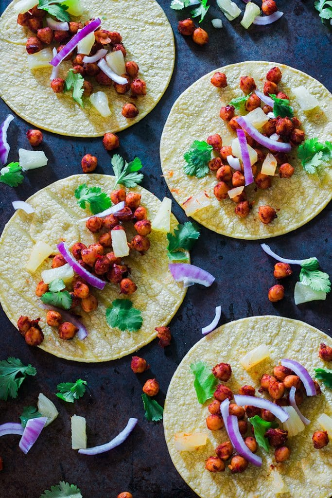 Tacos covered in cilantro and red onions.