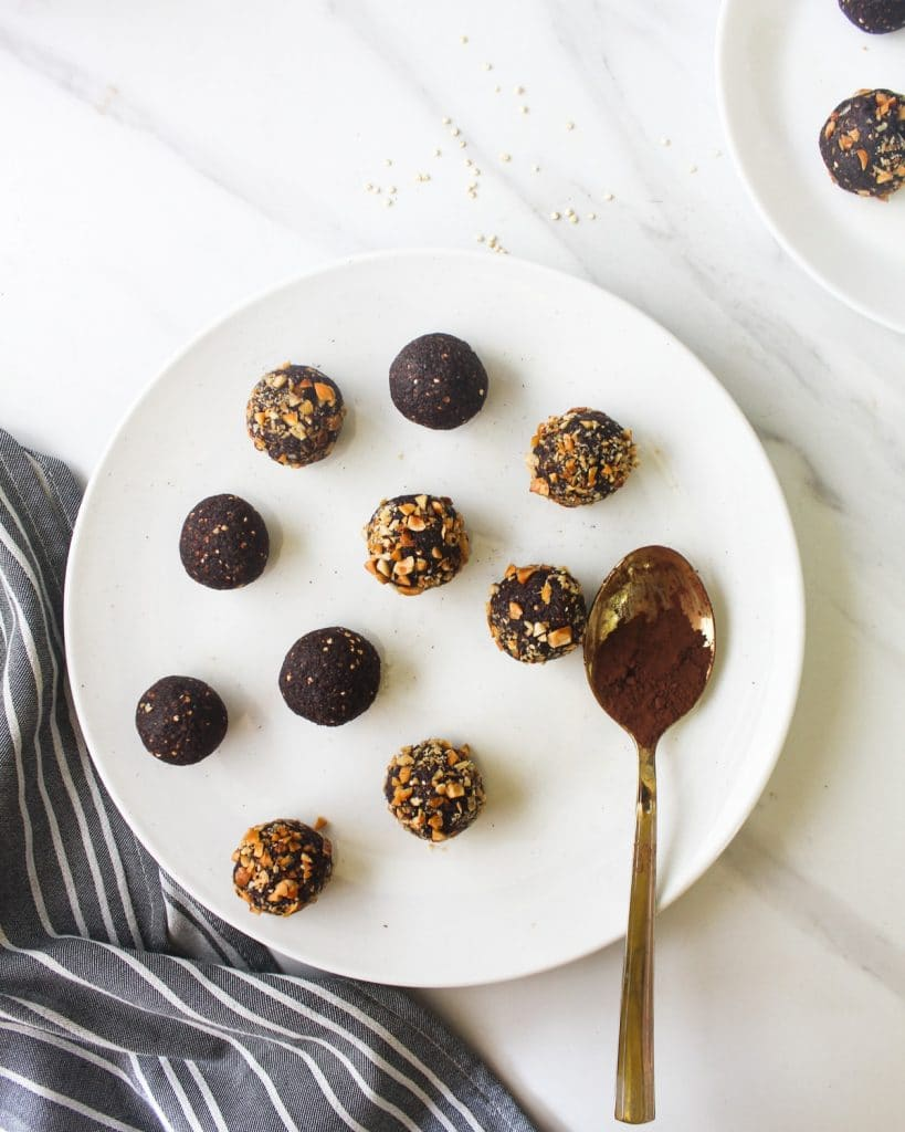 Chocolate bliss balls on a white plate.